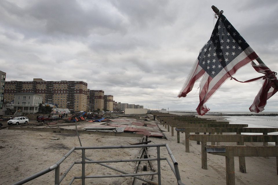 A damaged flag stands among the remnants of the boardwalk on Rockaway Beach the damage caused during hurricane Sandy, Wednesday, Oct. 31, 2012, in the Queens borough of New York. (AP Photo/Frank Franklin II) ORG XMIT: NYFF119