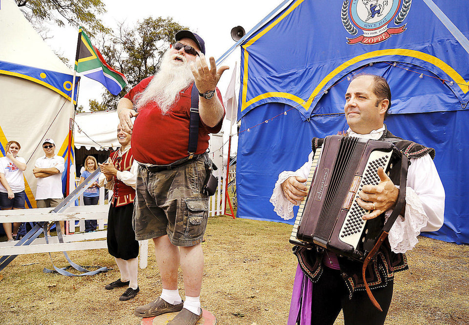 Photo - After asking a member of the Zoppe Italian Family Circus to play a song on his accordion, Bob Moore of Piedmont, was pulled from the crowd and invited to stand on a drum to sing the song while accordionist Jay Walther provided the tune.  Photo  by Jim Beckel, The Oklahoman.  Jim Beckel - THE OKLAHOMAN