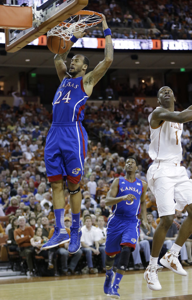 Kansas' Travis Releford (24) scores as Texas' Sheldon McClellan defends during the second half of an NCAA college basketball game, Saturday, Jan. 19, 2013, in Austin, Texas. Kansas won 64-59. (AP Photo/Eric Gay)