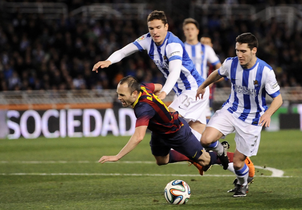 Photo - FC Barcelona's Andres Iniesta, left, is tackled by Real Sociedad's Mikel Gonzalez, right, and falls inside of penal area,  during their Spanish Copa del Rey semifinal second leg soccer match against Real Sociedad, at Anoeta stadium, in San Sebastian northern Spain, Wednesday, Feb. 12, 2014. (AP Photo/Alvaro Barrientos)