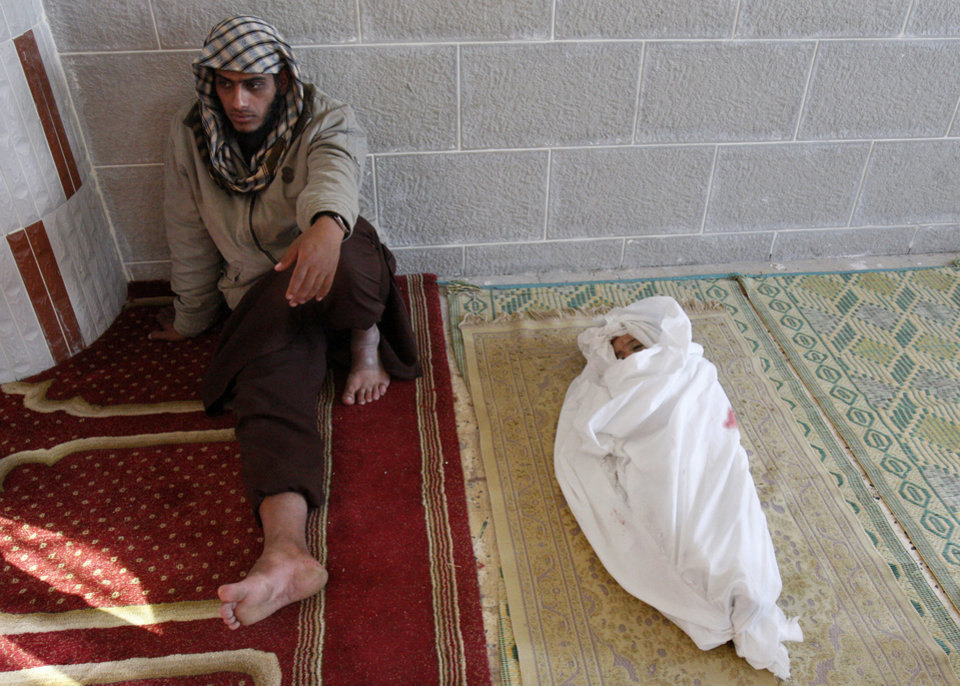 A Palestinian man sits next to the body of his year-and-a-half old son Iyad Abu Khoussa, during his funeral in Bureij Refugee Camp, central Gaza Strip, Sunday, Nov. 18, 2012. The baby boy was one of five Palestinian children killed in Israeli strikes on Sunday, according to a Gaza health official. (AP Photo/Adel Hana)