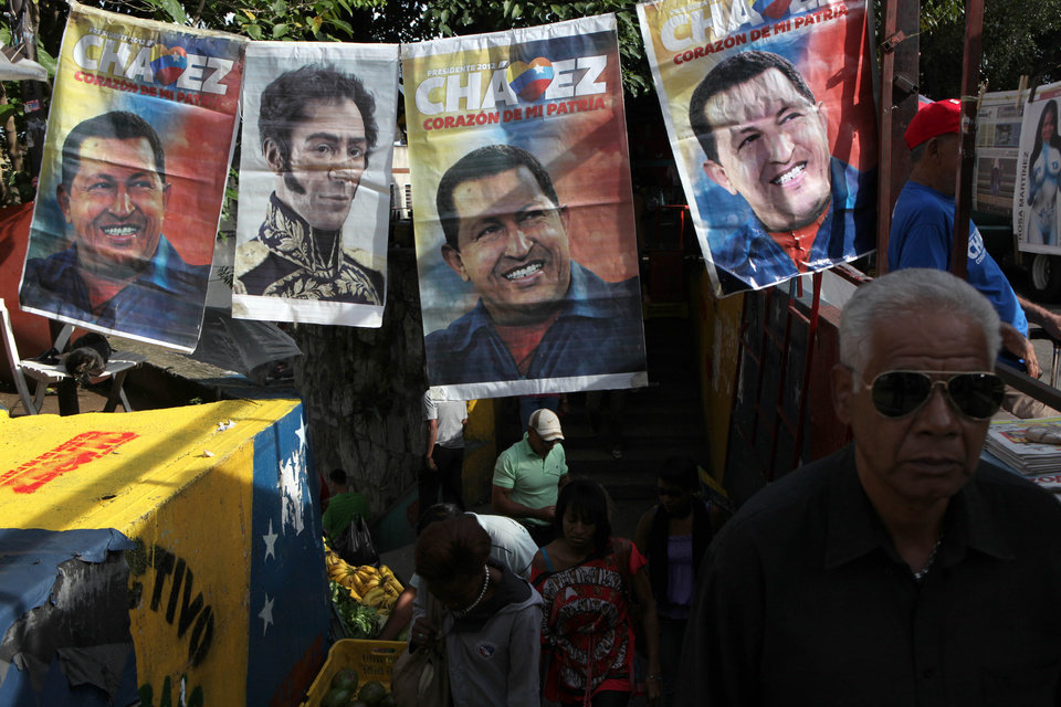 People walk by election campaign posters of President Hugo Chavez and a picture of independence hero Simon Bolivar in Caracas, Venezuela, Saturday, Oct. 6, 2012. Chavez is running for re-election against opposition candidate Henrique Capriles in Sunday\'s presidential election. (AP Photo/Rodrigo Abd)