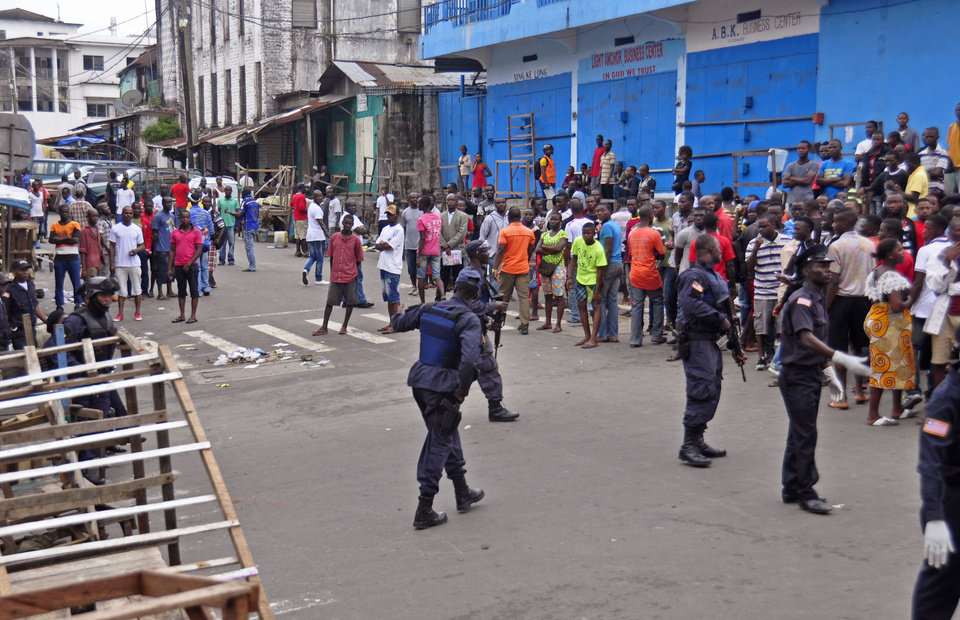 Photo - Liberia security forces, blockade an area around the West Point Ebola center as the government clamps down on the movement of people to prevent the spread of the Ebola virus in city Monrovia, Liberia, Wednesday, Aug. 20, 2014. Security forces deployed Wednesday to enforce a quarantine around a slum in the Liberian capital, stepping up the government's fight to stop the spread of Ebola and unnerving residents. (AP Photo/Abbas Dulleh)
