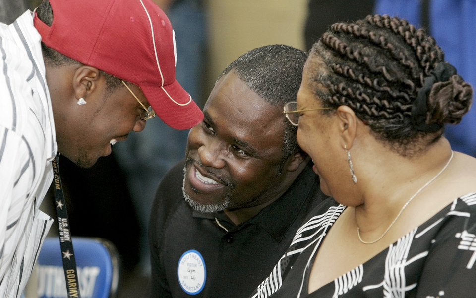 Photo - COLLEGE FOOTBALL SIGNING DAY: Gerald McCoy, Southeast Spartan football player, left, talks with his parents, Gerald McCoy, Sr., and Pat McCoy, after signing with the University of Oklahoma (OU) Sooners during an assembly at the Southeast High School gym in Oklahoma City, Wednesday, February 1, 2006. By Nate Billings, The Oklahoman