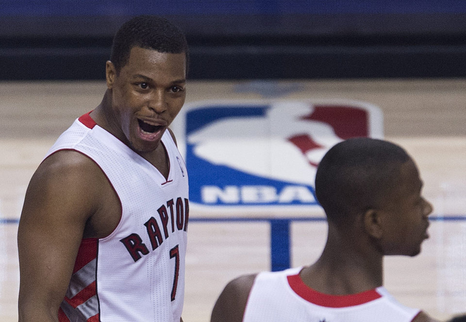 Photo - Toronto Raptors guard Kyle Lowry, left, reacts with teammate Terrence Ross, right, as they play against the Brooklyn Nets during the second half of Game 5 of the opening-round NBA basketball playoff series in Toronto, Wednesday, April 30, 2014. (AP Photo/The Canadian Press, Nathan Denette)