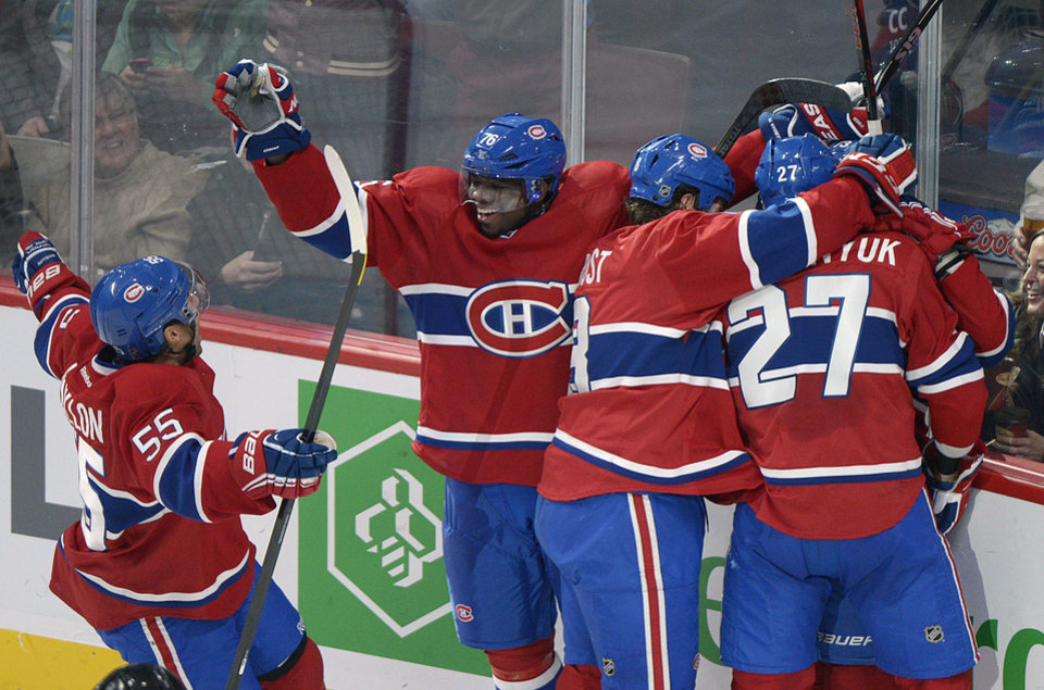 Montreal Canadiens\' PK Subban (76), Francis Bouillon (55), Brandon Prust (8), and Alex Galchenyuk (27) celebrate a goal by teammate Brendan Gallagher, hidden, during the second period of an NHL hockey game against the Buffalo Sabres in Montreal, Saturday ,Feb. 2, 2013. (AP Photo/The Canadian Press, Graham Hughes)