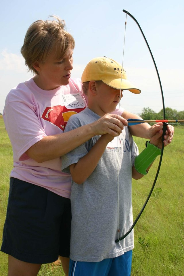 "Summer day camp director and physical therapist Jennifer Woodruff shows James ""Bo"" Cochran, of Norman, how to set up his bow and arrow during an archery session at the J. D. McCarty Center's Movin' & Groovin' summer day camp. Archery was just one of several activities the campers participated in during the week long camp.<br/><b>Community Photo By:</b> Greg Gaston<br/><b>Submitted By:</b> Greg,"