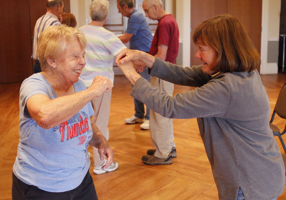 Photo - Betty Windsor, left, and Patty Snyder practice self defense techniques during a basic awareness self defense class by Gene Schultingkemper, a 6th degree black belt, at the Edmond Senior Center. PHOTO BY PAUL HELLSTERN, THE OKLAHOMAN.  PAUL HELLSTERN - Oklahoman