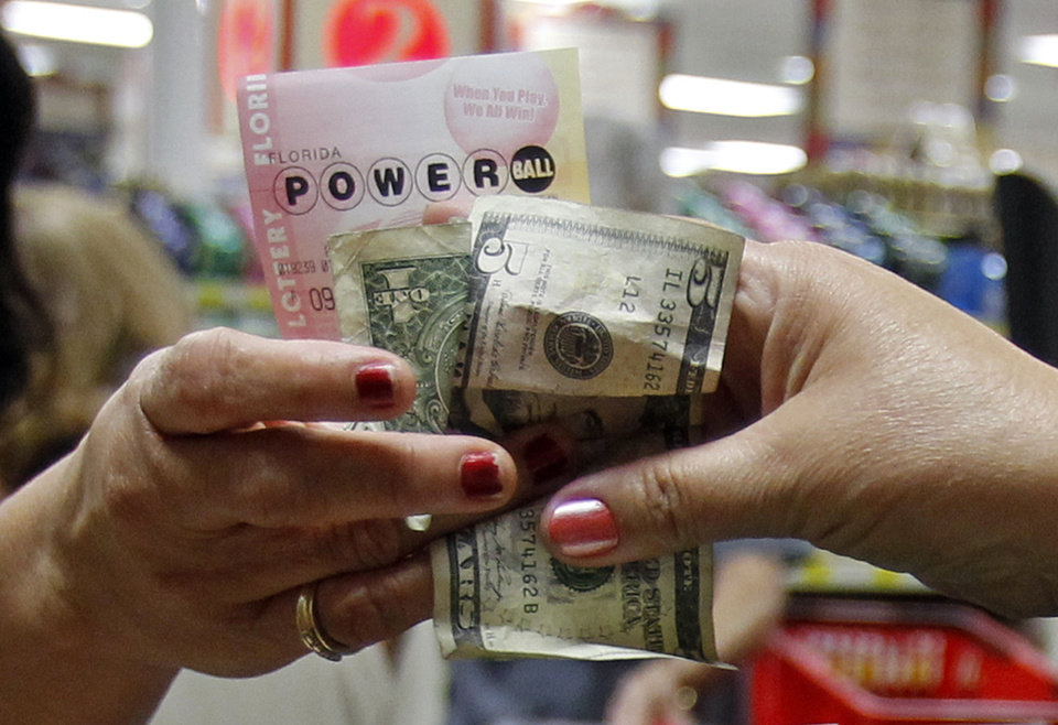 Photo -   A customer buys three Powerball tickets at a local supermarket in Hialeah, Fla.,Tuesday, Nov. 27, 2012. There has been no Powerball winner since Oct. 6, and the jackpot already has reached a record level for the game. Already over $500 million, it is the second-highest jackpot in lottery history, behind only the $656 million Mega Millions prize in March. (AP Photo/Alan Diaz)
