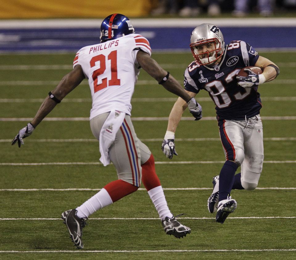 Photo - New England Patriots wide receiver Wes Welker (83) runs with the ball as he tries to avoid New York Giants strong safety Kenny Phillips (21) during the second half of the NFL Super Bowl XLVI football game, Sunday, Feb. 5, 2012, in Indianapolis. (AP Photo/Elise Amendola) ORG XMIT: SB434