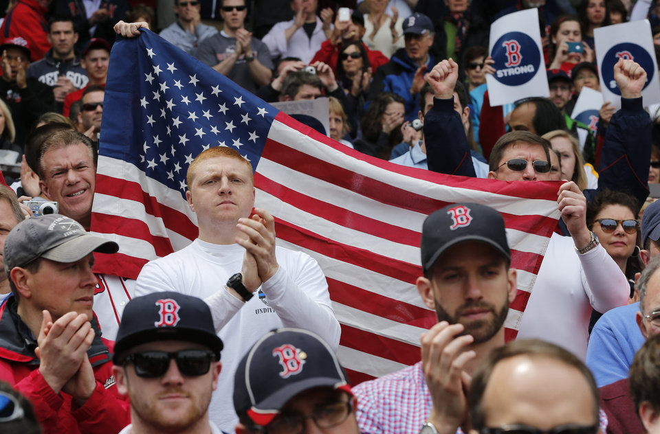 Fans hold a U.S. flag before a baseball game between the Boston Red Sox and the Kansas City Royals in Boston, Saturday, April 20, 2013. Playing at home for the first time since two explosions at the Boston Marathon finish line killed three people and wounded more than 180 others, the Red Sox honored the victims and the survivors with a pregame ceremony and an emotional video of scenes from Monday\'s race. (AP Photo/Michael Dwyer) ORG XMIT: MAMD149