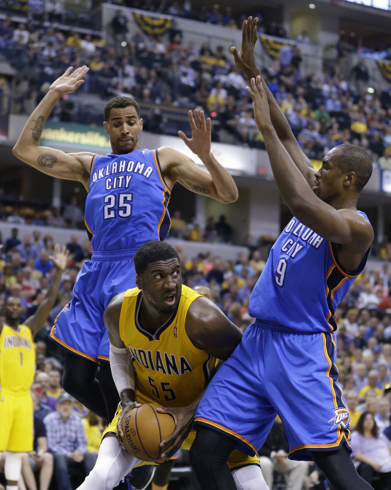 Photo - Indiana Pacers center Roy Hibbert, center, is trapped between Oklahoma City Thunder guard Thabo Sefolosha (25) and forward Serge Ibaka in the second half of an NBA basketball game in Indianapolis, Sunday, April 13, 2014. The Pacers defeated the Thunder 102-97. (AP Photo/Michael Conroy)