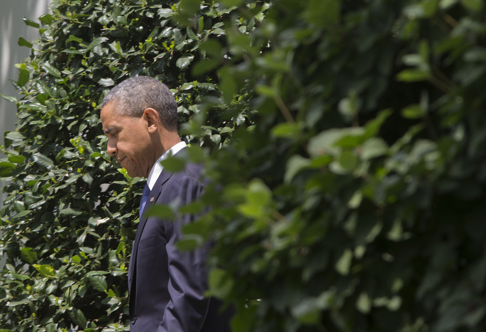 Photo - President Barack Obama walks out of the Oval Office of the White House in Washington, Friday, June 13, 2014, to walk to the South lawn to talk about his administration's response to a growing insurgency foothold in Iraq, prior to boarding the Marine One Helicopter on the South Lawn for Andrews Air Force Base, Md., then onto North Dakota and California. (AP Photo/Pablo Martinez Monsivais)