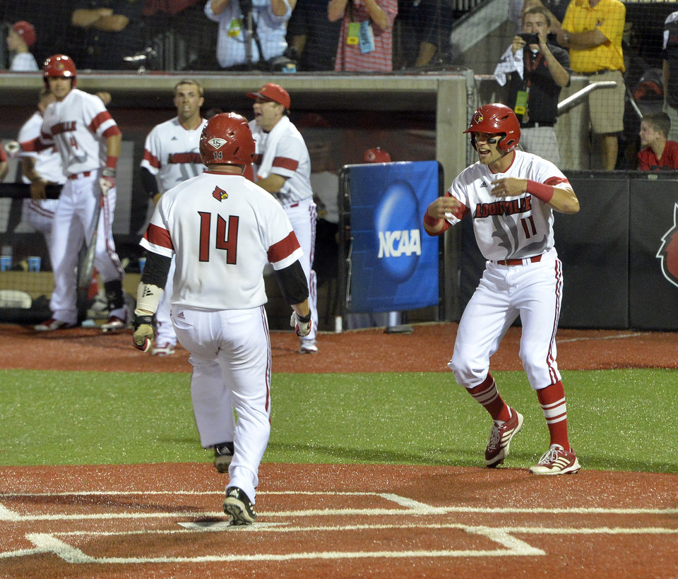 Photo - Louisville's Zach Lucas, right, waives teammate Kyle Gibson across home scoring two runs in the bottom of the eighth inning of an NCAA college baseball tournament super regional game against Kennesaw State in Louisville, Ky., Friday, June 6, 2014. Louisville won 5-3. (AP Photo/Timothy D. Easley)