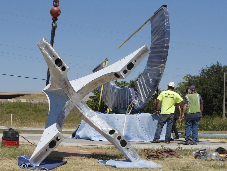 Photo - Workers prepare the various components of a large metal sculpture called