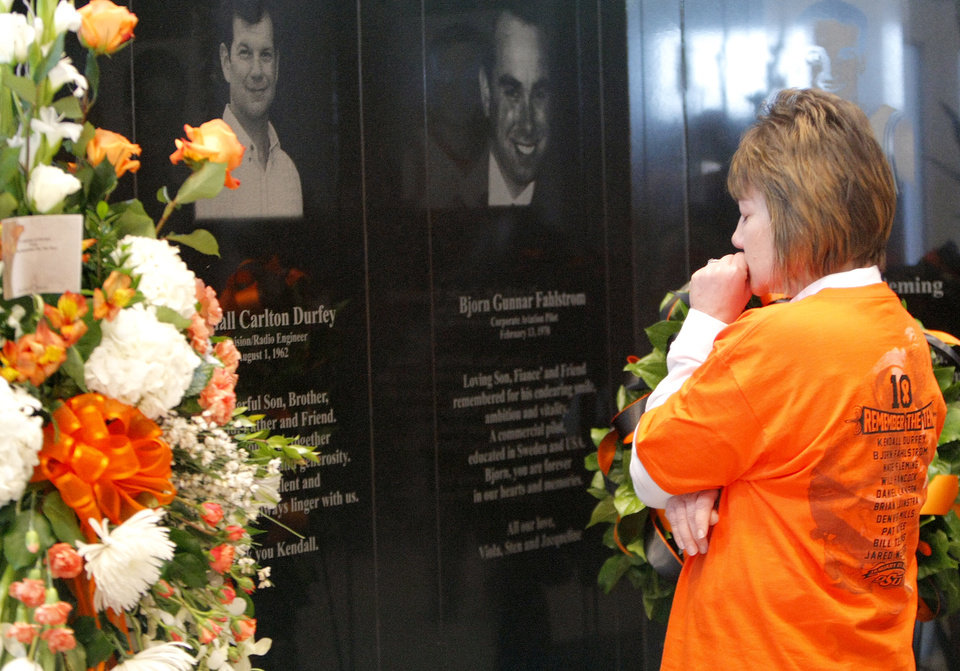 Photo - Karlene Durfey pauses at the memorial of her brother, Kendall Carlton Durfey, before the basketball game between Oklahoma State and Texas, Wednesday, Jan. 26, 2011, at Gallagher-Iba Arena in Stillwater, Okla. Photo by Sarah Phipps, The Oklahoman