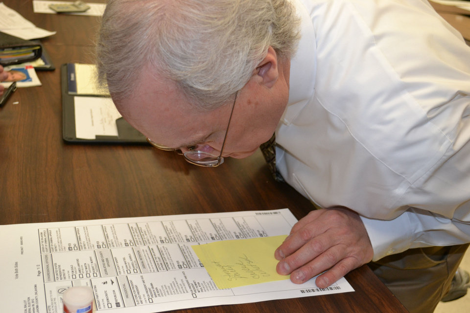 Doug Sanderson, secretary of the Oklahoma County Election Board, tries to interpret a subtle marking on a ballot Wednesday during a recount of the Nov. 6 county sheriff election. PHOTO BY ZEKE CAMPFIELD, THE OKLAHOMAN