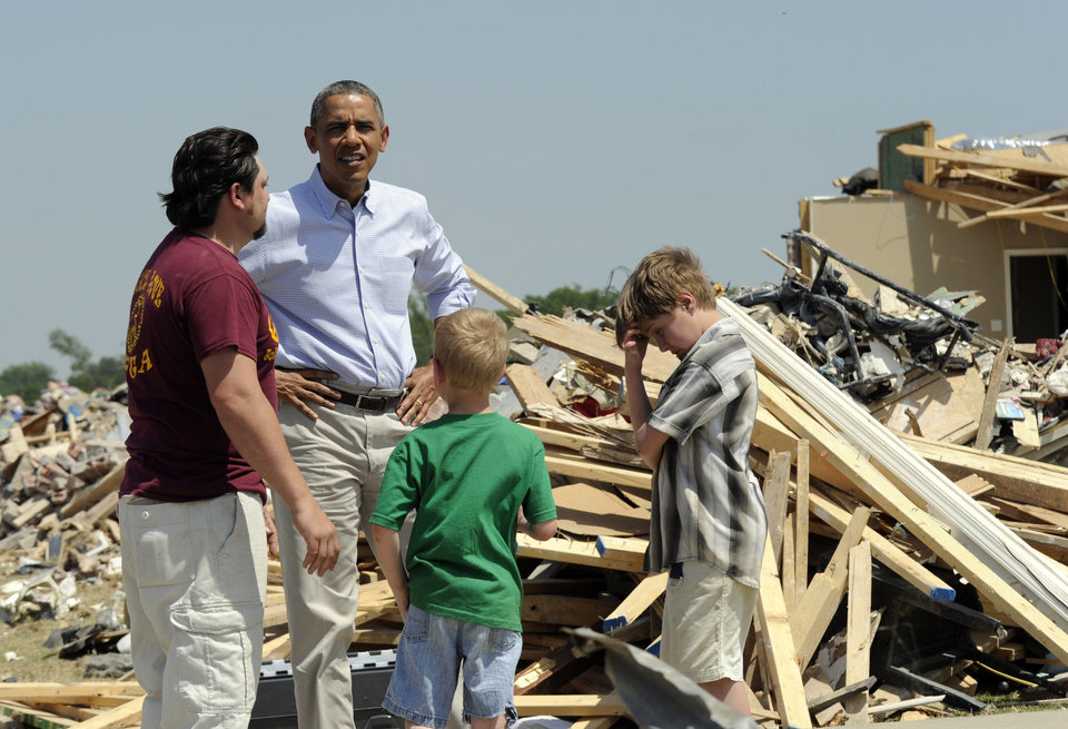 Photo - President Barack Obama tours tornado-damaged areas of Vilonia, Ark., Wednesday, May 7, 2014, and talks with Daniel Smith and his sons Garrison Dority and Gabriel Dority, right. Obama is visiting with first responders and families affected by the recent tornados before traveling on to California where he will raise money for the Democratic Party and receive an award from a foundation created by movie director Steven Spielberg. (AP Photo/Susan Walsh)