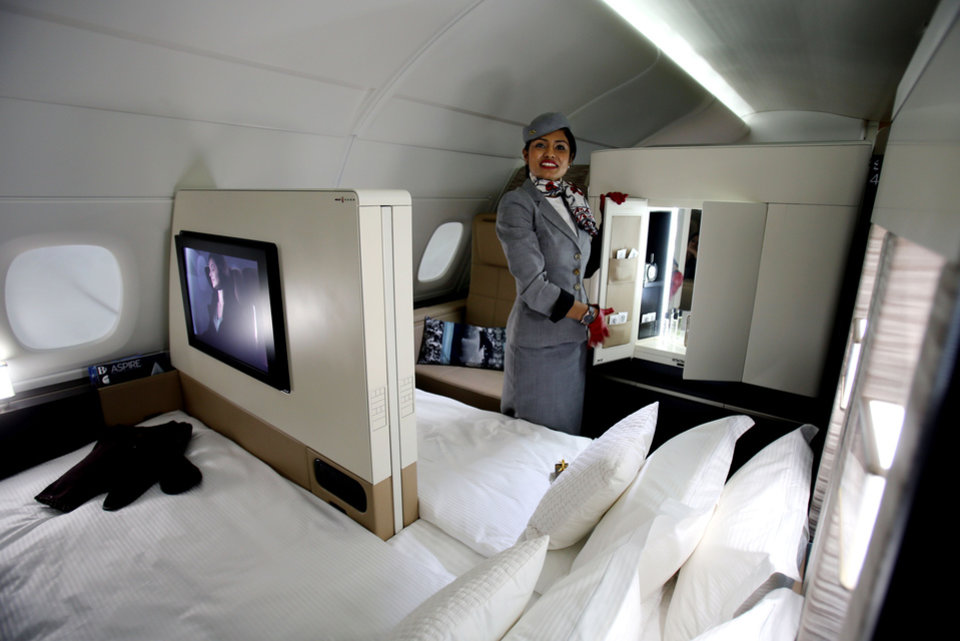 An Etihad Airways official stands inside the 125-square-foot (11.61-square-meter) area that includes a �living room� partitioned off from the first-class aisle, leather seating, a chilled minibar and a 32-inch flat-screen TV, at a training facility in Abu Dhabi, United Arab Emirates, Sunday, May 4, 2014. Etihad Airways, a fast-growing Mideast carrier, laid out plans Sunday to offer passengers who find first-class seats a bit too tight a miniature suite featuring a closed-off bedroom, private bathroom and a dedicated butler. (AP Photo/Kamran Jebreili)