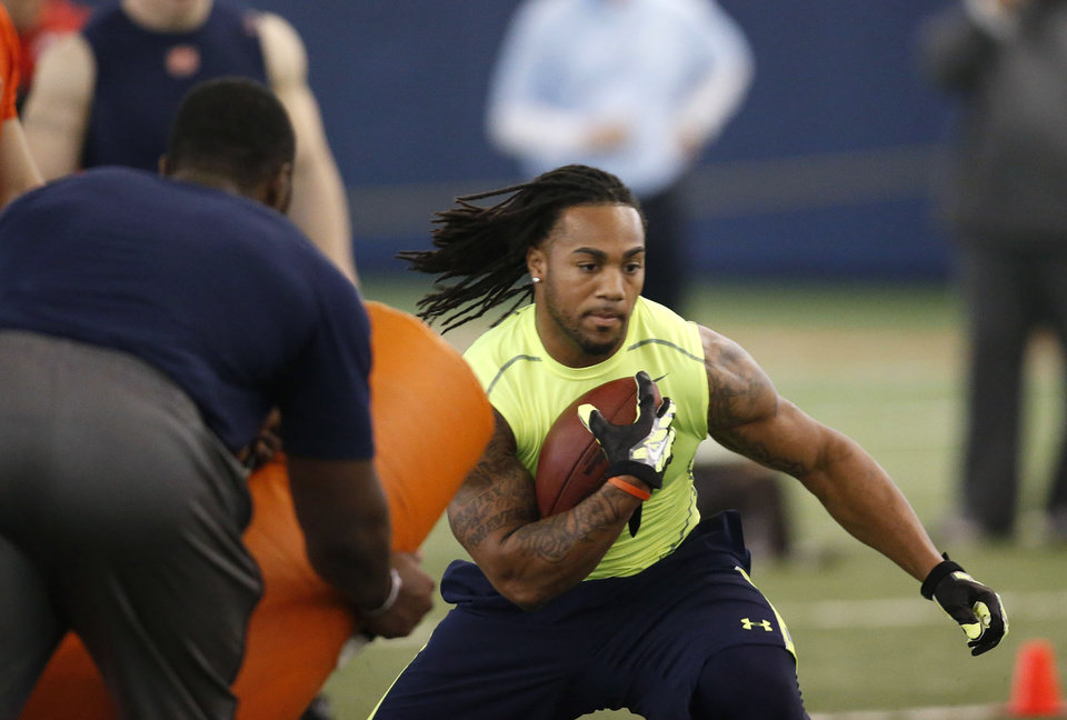 Photo - Heisman Trophy finalist Tre Mason runs a drill at at Auburn's pro day for NFL football scouts, Tuesday, March 4, 2014, in Auburn, Ala. (AP Photo/Hal Yeager)