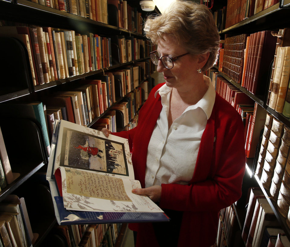 "Janet Croft, head of access services at the University of Oklahoma's Bizzell Memorial Library, looks at a J.R.R. Tolkien book at the library. An expert on Tolkien, she received a screen credit line in ""The Hobbit."" Photo by Steve Sisney, The Oklahoman"