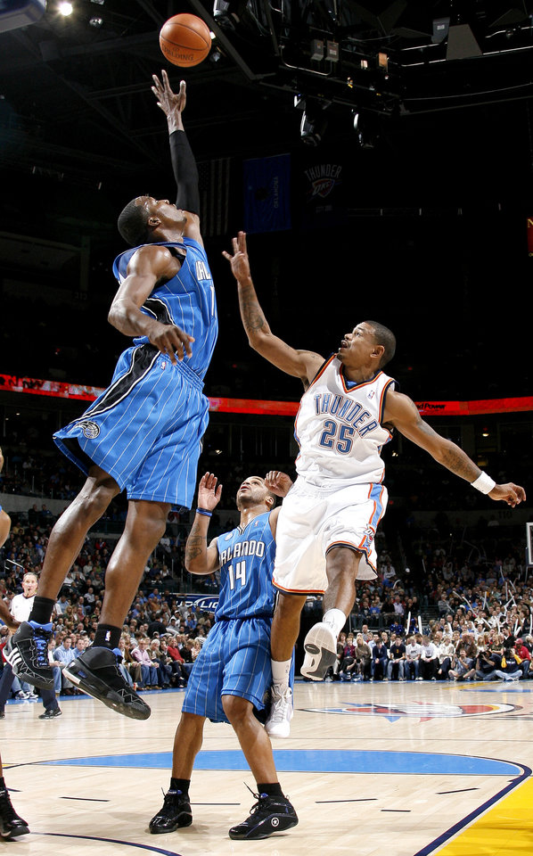 Photo - Oklahoma City's Earl Watson tries to get a shot over Dwight Howard of Orlando as Jameer Nelson watches during the NBA basketball game between the Oklahoma City Thunder and the Orlando Magic at the Ford Center in Oklahoma City, Wednesday, Nov. 12, 2008. BY BRYAN TERRY, THE OKLAHOMAN   ORG XMIT: KOD