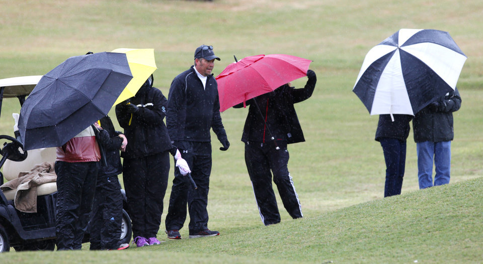 Photo - Spectators used umbrellas to keep the wind and rain off during the second day of Girls 6A golf tournament at River Oaks Golf Club, Thursday, May 2, 2013. Photo By David McDaniel/The Oklahoman