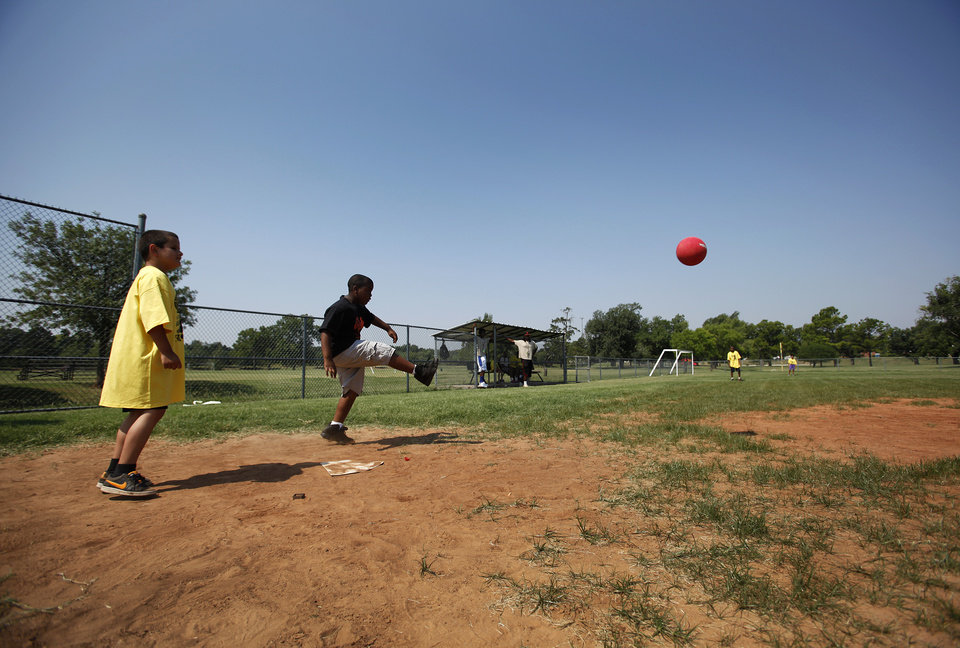 Quadre Galbreath, 8, kicks a ball during a kickball tournament hosted by the Oklahoma City Police Department at South Rotary Park in Oklahoma City, Wednesday, June 27, 2012.  Photo by Garett Fisbeck, The Oklahoman