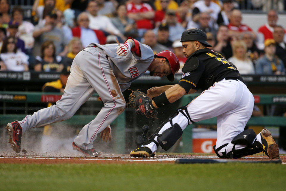 Photo - Cincinnati Reds' Billy Hamilton (6), left, scores ahead of the tag by Pittsburgh Pirates catcher Russell Martin (55) during the first inning of a baseball game in Pittsburgh Monday, April 21, 2014. Hamilton scored on a fielder's choice by teammate Brandon Phillips. (AP Photo/Gene J. Puskar)