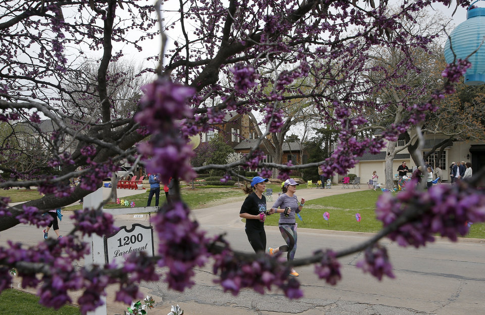 Photo -  Runners in the 10k race Sunday pass by a redbud tree in bloom. [Photo by Sarah Phipps, The Oklahoman]