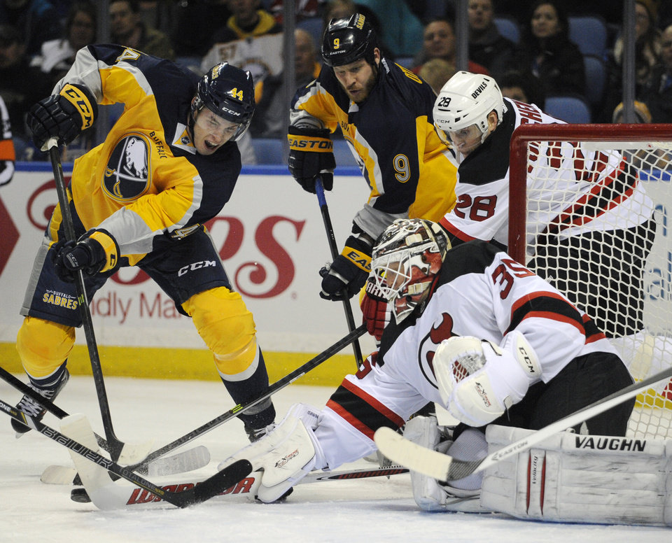 Photo - Buffalo Sabres' Brayden McNabb (44) and Steve Ott (9) battle for a rebound with New Jersey Devils' Anton Volchenkov (28), of Russia, and Cory Schneider (35) during the first period of an NHL hockey game in Buffalo, N.Y., Saturday, Jan. 4, 2014. (AP Photo/Gary Wiepert)