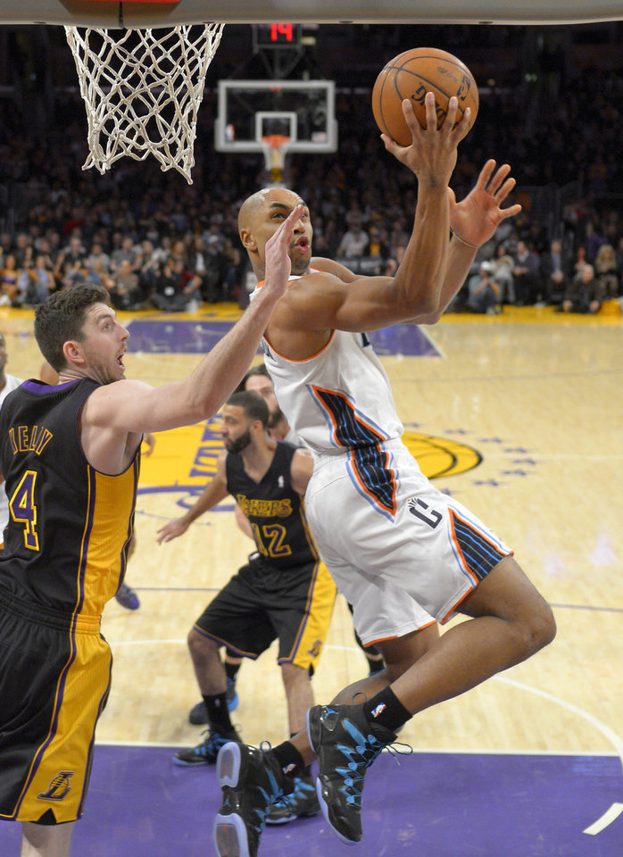 Photo - Charlotte Bobcats guard Gerald Henderson, right, puts up a shot as Los Angeles Lakers forward Ryan Kelly defends during the first half of an NBA basketball game, Friday, Jan. 31, 2014, in Los Angeles. (AP Photo/Mark J. Terrill)