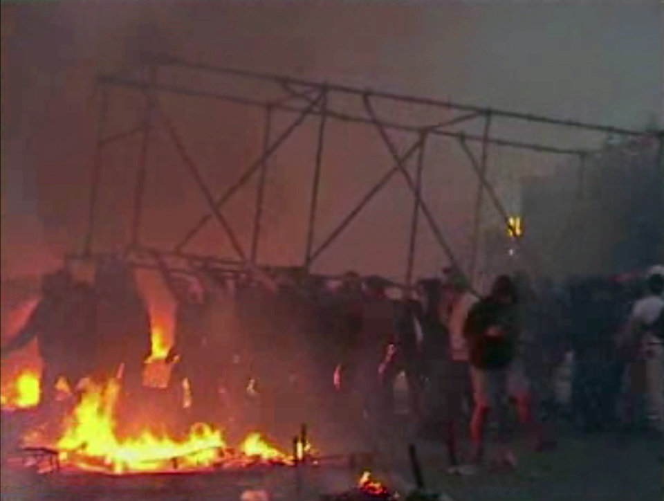 Photo - This image made from AP video shows people carrying a scaffolding frame through fires on the ground in Odessa, Ukraine, on Friday, May 2, 2014. Deadly clashes took place in the southern Ukraine port of Odessa on Friday, triggered by Ukraine's offensive to recapture the eastern city of Slovyansk from pro-Russia forces. (AP Photo via AP Video)
