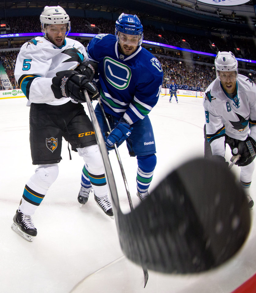 San Jose Sharks' Jason Demers, left, and Vancouver Canucks' Brad Richardson vie for the puck as Sharks' Joe Pavelski, right, watches during the first period of an NHL hockey game, Thursday, Nov. 14, 2013 in Vancouver, British Columbia.  (AP Photo/The Canadian Press, Darryl Dyck)