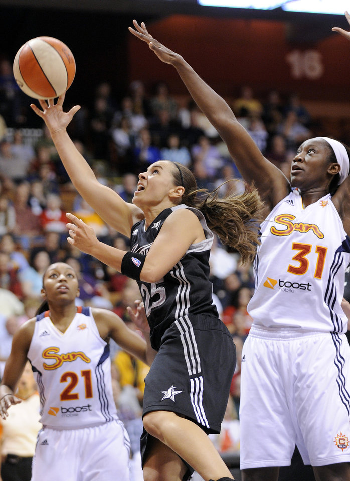 Photo - San Antonio Silver Stars' Becky Hammon, left, drives past Connecticut Sun's Tina Charles during the first half of their WNBA basketball game in Uncasville, Conn., Friday, May 25, 2012. (AP Photo/Fred Beckham)
