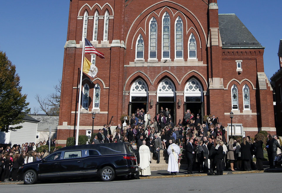 Photo - Mourners leave St. Augustine Church in Andover, Mass., Monday Oct. 28, 2013 after the funeral service for slain Danvers High School teacher Colleen Ritzer. Colleen Ritzer, 24, who taught math at Danvers High School, was killed in a school bathroom after dismissal Oct. 22, police said. Her body was found in woods behind the school. Philip Chism, 14, has pleaded not guilty to a murder charge. (AP Photo/Elise Amendola)