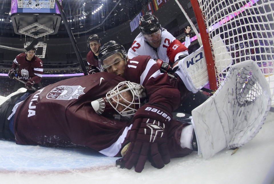 Photo - Latvia defenseman Kristaps Sotnieks  reaches over Latvia goaltender Kristers Gudlevskis to grab the puck and keep it from completely crossing the goal line during the third period of a men's ice hockey game against Canada at the 2014 Winter Olympics, Wednesday, Feb. 19, 2014, in Sochi, Russia. The goal was disallowed and ruled dead. Canada won 2-1. (AP Photo/Bruce Bennett, Pool)