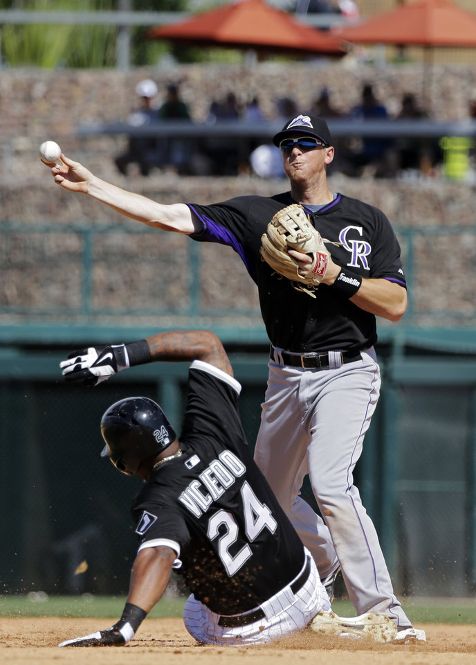 Photo - Colorado Rockies second baseman DJ LeMahieu throws over Chicago White Sox's Dayan Viciedo (24) to complete a double play on Alexei Ramirez in the fifth inning of a spring exhibition baseball game Tuesday, March 25, 2014, in Glendale, Ariz. (AP Photo/Mark Duncan)