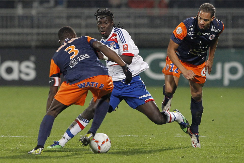 Photo - Lyon's Bafe Gomis, center, challenges for the ball with Montpellier's Mapou Yangambiwa, left, and Daniel Congre, right, during their French League One soccer match at Gerland stadium, in Lyon, central France, Saturday, Dec. 1, 2012. (AP Photo/Laurent Cipriani)