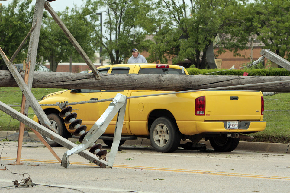 A pickup remains stuck under power poles on Saturday, April 14, 2012, in Norman, Okla. Twenty Fourth Avenue was still closed following Friday\'s tornado. Photo by Steve Sisney, The Oklahoman