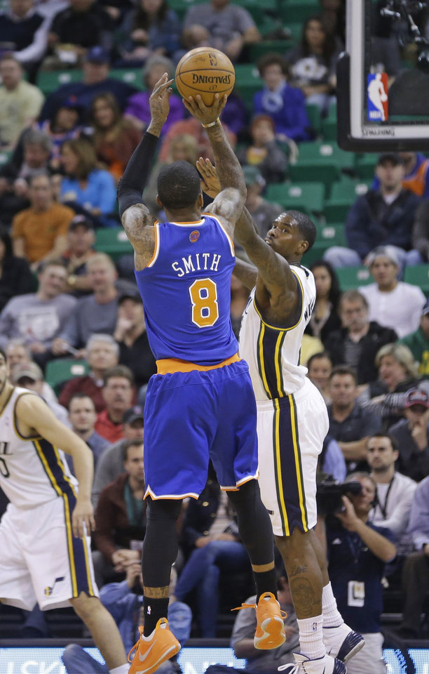 Photo - New York Knicks' J.R. Smith (8) shoots as Utah Jazz's Marvin Williams, rear, defends in the first quarter during an NBA basketball game Monday, March 31, 2014, in Salt Lake City. (AP Photo/Rick Bowmer)