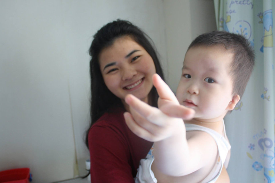 "Photo -  An orphan known as Jia Jia and Deer Creek High School student Abigale ""Abbey"" White pose for a picture together at the China Care Home where the child resides in Beijing. Photo provided"