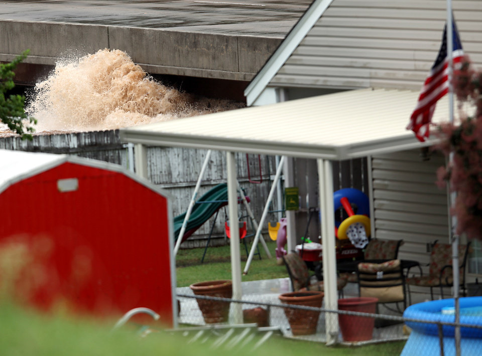 Photo - Water splashes up near Hefner Road at the Ski Island neighborhood south of Hefner between Macarthur and Rockwell in Oklahoma City on Monday, June 14, 2010. Photo by John Clanton, The Oklahoman