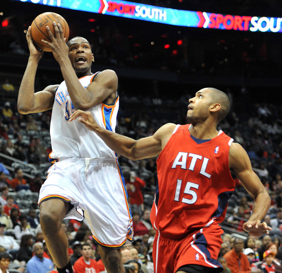 Photo - Oklahoma City Thunder's Kevin Durant, left, goes to the basket against Atlanta Hawks' Al Horford (15) in the third quarter of an NBA basketball game in Atlanta, Monday, Jan. 18, 2010. The Thunder won 94-91 and Durant scored 29 points. AP PHOTO