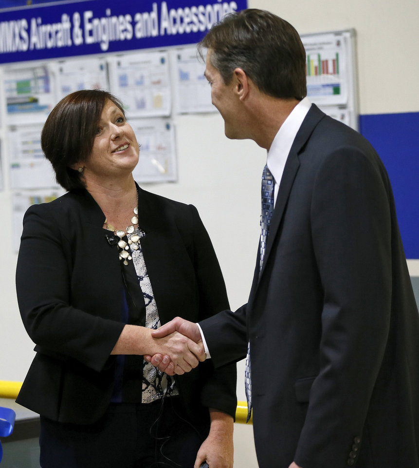 Photo -  Maria Donovan, program manager at General Atomics Aeronautical, left, and Kevin O'Connor, vice director of the Oklahoma City Air Logistics Complex, shake hands Wednesday during a ribbon-cutting ceremony announcing a program for the test and repair of an ignition switch component for unmanned aerial vehicles at Tinker Air Force Base. Photo by Nate Billings, The Oklahoman   NATE BILLINGS -