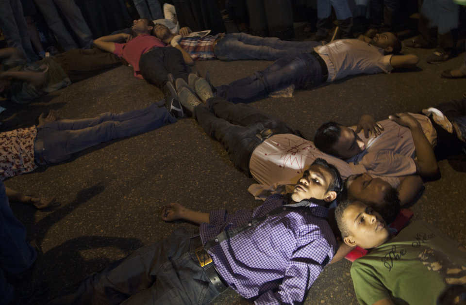 "Egyptian protesters lay on the ground depicting a cross during a march marking the first anniversary of the victims who were killed during clashes with the military police in front of the National State T.V. building, known as Maspero, in Cairo, Egypt, Tuesday, Oct. 9, 2012. Muslim clerics, Christian priests, activists and former liberal lawmakers were among those marching to mark the anniversary of the ""Maspero massacre,"" referring to the name of the state TV building, where the clashes broke out. (AP Photo/Khalil Hamra)"