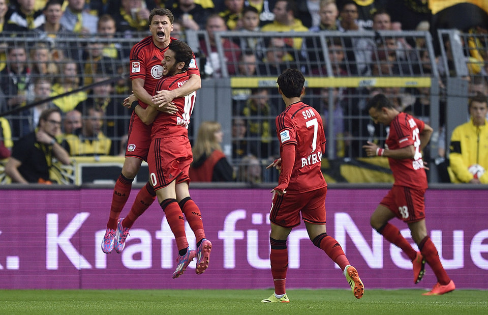 Photo - Leverkusen's Sebastian Boenisch from Poland, Hakan Calhanoglu from Turkey and Son Heung-min from South Korea, from left, celebrate the opening goal after ten seconds by Leverkusen's Karim Bellarabi, right, during the German Bundesliga soccer match between Borussia Dortmund and Bayer Leverkusen in Dortmund,  Germany, Saturday, Aug. 23, 2014.. (AP Photo/Martin Meissner)