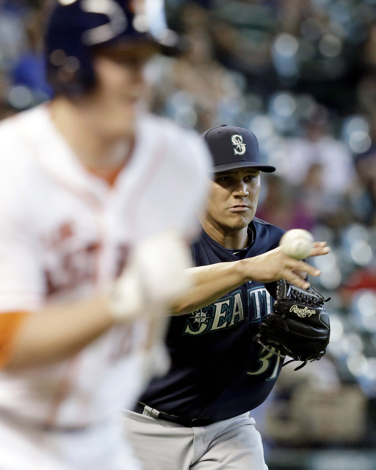 Photo - Seattle Mariners relief pitcher Yoervis Medina, right, throws to first base for the out on Houston Astros' Marc Krauss, left, in the eighth inning of a baseball game on Saturday, May 3, 2014, in Houston. Seattle won 9-8. (AP Photo/Pat Sullivan)
