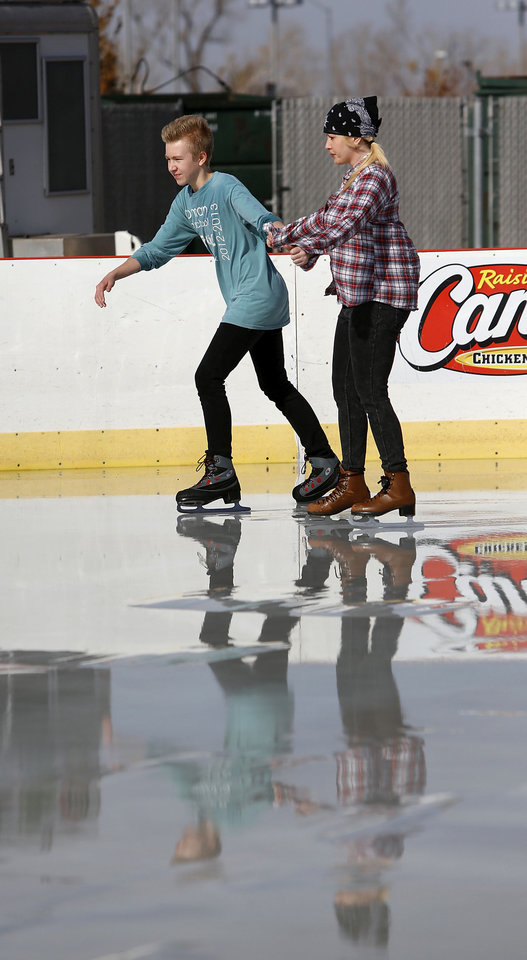 Photo - Austin Pruett and his mother, Melissa Kissner, both of Norman, skate Saturday at the community outdoor skating rink open for the holiday season at Marc Heitz Chevrolet. PHOTO BY JIM BECKEL, THE OKLAHOMAN  Jim Beckel