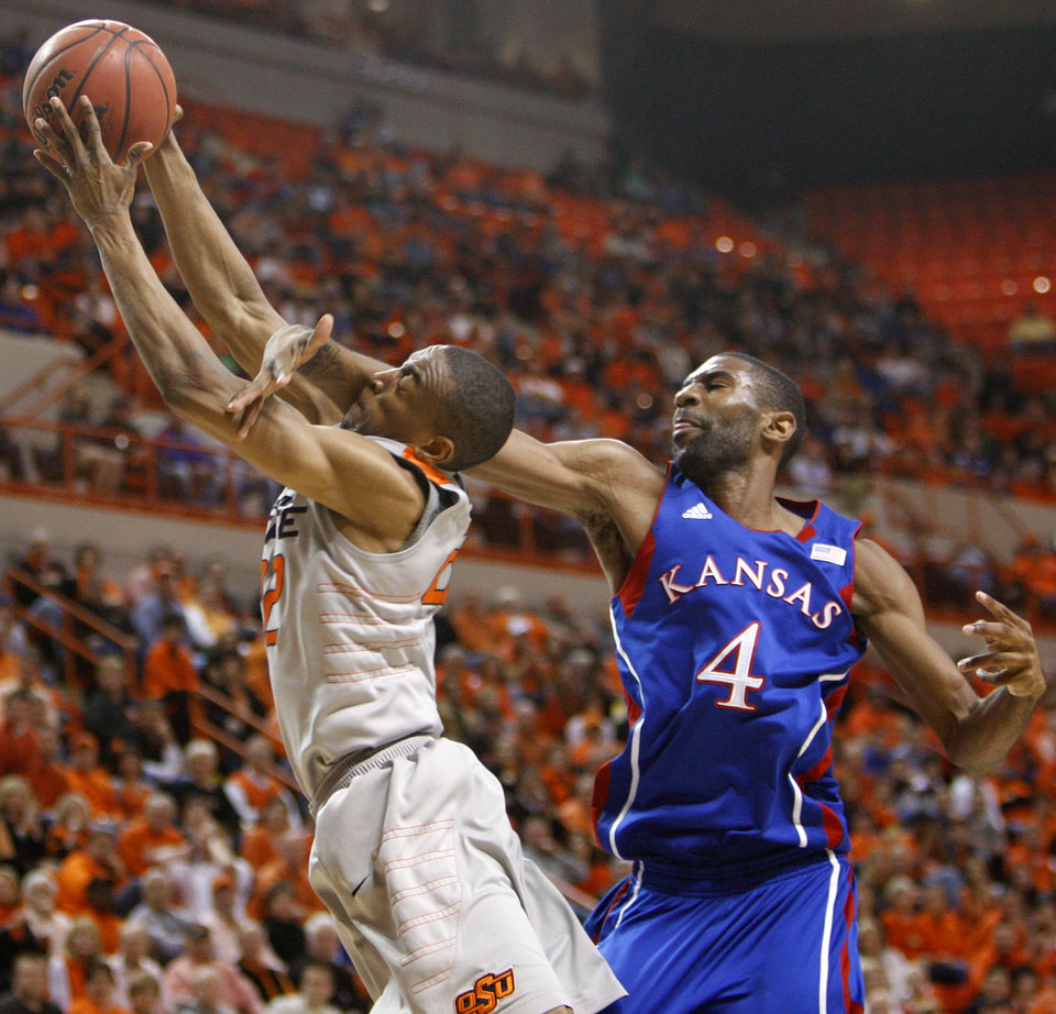 Photo - OSU's Markel Brown (22) is fouled by KU's Justin Wesley (4) in the first half during a men's college basketball game between the Oklahoma State University Cowboys and the University of Kansas Jayhawks at Gallagher-Iba Arena in Stillwater, Okla., Monday, Feb. 27, 2012. Photo by Nate Billings, The Oklahoman
